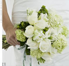"""Viburnum, parrot tulips, ranunculus, roses, hypericum berries, and camellia in white and green were wrapped with a ribbon printed with the couple's wedding quote: """"Don't take a whole day to recognize sunshine."""""""