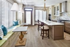 This transitional townhouse in Cherry Creek, Colo. uses soft browns and creams to create an elegant, flowing design. A window seat is paired with traditional tables and pendant lights for a casual eating spot, while the kitchen island provides another dining area. Cream upper cabinets contrast against the mocha cabinets, while a brass chandelier adds a touch of glam.