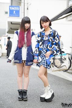 """Jusnan(right) 17, student. Mickey Mouse print jacket over a resale top and gingham skirt. Her teapot bag is by Q-Pot and her platform lace-up boots are Murua. Earrings, a heart necklace and bracelets from Q-Pot, a smiley face backpack, and Avantgarde tights. Hinatan(left) 18 years old and she's a freeter. Varsity jacket from Spinns with a hoodie and a skirt from min plume. Her backpack is Sanrio and her """"mermaid"""" sneakers are L.D.S. Her egg hair pin and other accessories are from Artemis…"""