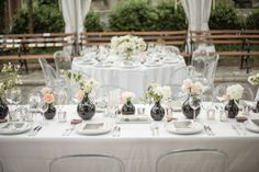 If you care for a uniform tablescape that doesn't look uniform, vary the vase sizes and alternate between two flower hues throughout the table. This setup offers variety for the eye, while soothing those who prefer precisely organized table settings. Via Ang Weddings