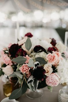 Lush floral arrangement  with pinks, blush, champagne, ivory with pops of deep velvety maroon and purple flowers set in the middle of a guest table set for a full seated dinner. Lovely outdoor California Tent Wedding. Photo by Feather + North and Erin Northcutt Photography, Wedding Planning by Bella Baxter Events, Floral by Ena Fowler Floral Design, Rentals by Classic Party Rentals and BBJ Linen. Venue by Wente Vineyards.