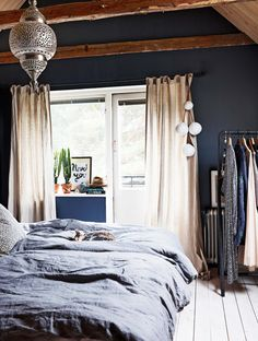 Bedroom with dark walls and exposed beams