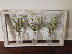 Wall art: old window frame, chicken wire, old bottles and greenery