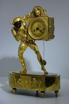 """Très jolie pendule d'époque Empire, en bronze doré, mat, et bruni. Le personnage masqué porte un costume à damier. Il soutient sur sa hanche une caisse représentant un """"coucou"""". La base à bouts arrondis, est ornée au centre d'une scène d'intérieur avec cheminée, singe chat et enfant. Elle repose sur 5 patins de forme toupie. Le mouvement dont la suspension est à fil, sonne aux heures et demies."""