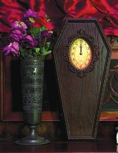 "COFFIN CLOCK Vintage ""toe pincher"" style coffin which features a viewing window which was common in the Victorian era. Recessed in these windows are unique distressed clock faces. Requires one AA battery. Clocks can hang on the wall or stand on any level surface. USA. 17"""