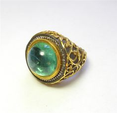 Emerald Ring - There is a large cabochon cut emerald that weighs 15.00ct. The sterling silver mounting is complimented by a beautiful 24kt yellow gold pattern. K508095 (subject to prior sale) – Lilliane's Jewelry – 4101 W. 83rd St. Prairie Village, KS 66208 – 913-383-3376 –