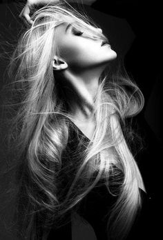 Amazing profile shot. Blonde hair is stark against black shirt and dark backdrop. Studio setting, photography, modeling.