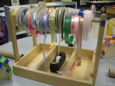 """This was originally a """"listening center"""" station. You'd place cassettes in the divided sections and hang the headphones on the rods. I got one of my handy dad's to help me figure out how to make the dowels removable. Another parent donated lots of ribbon and I thought it would make a great ribbon dispenser."""