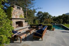 Gorgeous stone outdoor fireplace with climbing ivy, beside the crystal clear pool in this backyard. Discovered on porch.com