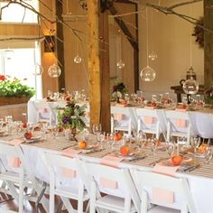 """A Vintage and Rustic Wedding in Carbondale, CO/The couple chose Flying Dog Ranch Retreat because they wanted their guests to experience the """"rustic, natural beauty of Colorado."""" To give the reception space (a converted barn) a fresh vibe, the room was dressed with farm-style tables, white chairs, peach and white linens, and hanging votives."""