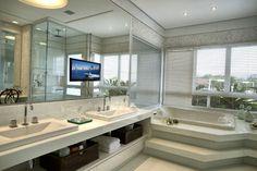 A sala de banho da suíte master conta com generosos espelhos e hidromassagem com vista para área de lazer externa. Para o projeto de interiores da casa Acapulco, a designer Bianka Mugnatto escolheu tons claros e clássicos