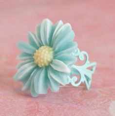 This vintage style variegated aqua blue, white and pale yellow daisy cabochon sits on a mint green filigree adjustable ring. $7.88 USD.