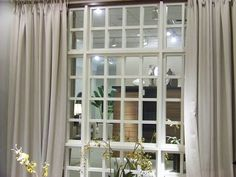 Great cure for a windowless room.  A paneled mirror ~ with the curtains on the side, doesn't it look like real windows?  Perfect for a windowless basement!