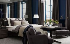 Bedroom with a wall of mirrors, a bed with lots of textiles, an armchair, floor lamps and fresh flowers