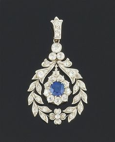 A Belle epoque platinum, sapphire and diamond pendant -  The central circular sapphire and old brilliant-cut diamond pear-shaped cluster drop within a diamond garland design frame to a diamond surmount and loop suspension, circa 1910.