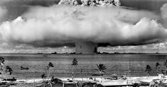 Bikini Atoll, 1946  A massive column of water rises from the sea as the U.S. detonate an atom bomb at Bikini Atoll in the Pacific in the first underwater test of the device. Note the aircraft carrier  (lower right hand of the column) being carried like a toy by the awesome strength of the blast.  July 25, 1946.