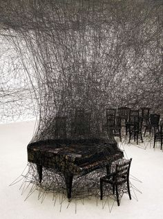 In Silence - Installation by Chiharu Shiota...The piece responds to an incident that occurred when Shiota was nine-years old. She woke in the night to sound of burning timber and ran to wake her parents. The family then watched helplessly as a neighbour's home burned. Later, Shiota saw the remains of a piano charred and silent in the ashes.