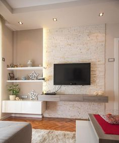 The TV looks great against this textured wall. Chasing wires in stone is a nightmare though. Think wood texture instead.