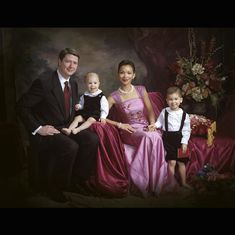 A beautiful Rembrandt style portrait.  Mom and Dad are dressed in formal attire with children's outfits coordinated.
