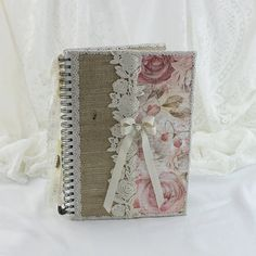 Please note i cannot gaurantee overseas deliveries to arrive before christmas after the 7th of december 2016.  This Lined Notebook features a hardback lined book which i have handpainted white and then covered with a burlap fabric along with a rose rice paper on the front. Lace bows and vintage style jewellery drape from the side. This notebook is ideal for jotting down notes,thoughts,ideas and more! A beautiful gift to give or receive. Please note the postage is quite high because of the…
