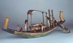 *EGYPT ~ Sycamore fig wood funerary boat model, 12th Dynasty, about 1900 BC. This painted wooden model represents a funerary boat bearing a mummy on a bier beneath a canopy. To the port side of the mummy stands the small figure of a man, holding in his left hand a partially unrolled papyrus. He is presumably a lector-priest, who would read the ritual text written on the papyrus over the body. There are actually some traces of a text on the papyrus, but it has not been possible to read it.