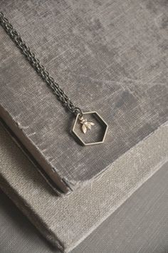 A little brass bee hangs inside a vintage raw brass hexagon. Hexagon measures approximately 0.75 wide. Antiqued brass chain measures 18. Length of chain can be adjusted upon request.
