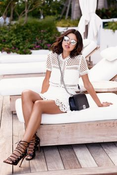 A white eyelet dress is worn with a crossbody Chanel bag, lace-up pumps, and mirrored Dior sunglasses