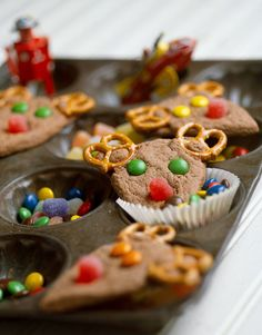 These cute cookies start with a chewy chocolate base. Your favorite chocolate candy makes the eyes, red gumdrops the nose, and salty pretzels the antlers. #christmascookies #forkids #cuteholidaycookieideas #easy #bhg