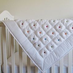 REALLY cute puff quilt (...But buttons and embellishments on a  baby quilt are unsafe unless they're appliqued securely down. Love the pop of color the buttons provide - what is an alternative to buttons to add that color and adorable tufted look?)