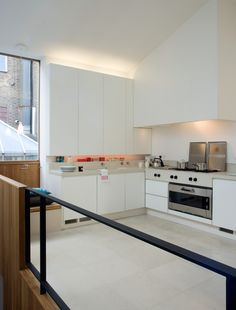 New Mews House | Jonathan Tuckey Design, West London, UK - The kitchen is finished with a cast terrazzo worktop & tiles. The balustrade is constructed from mild steel and lye treated oak.