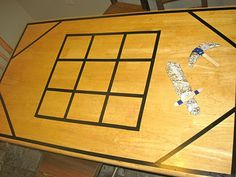 Create the Minecraft Crafting Table on your kitchen table using electrical tape...then have the kids craft swords and axes using cardboard forms, large popsicle sticks, and aluminum foil. Genius!
