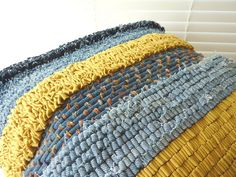 Rag Rug. Large cushion/pillow made using hooking, prodding and couching techniques. The textiles used include various pairs of repurposed denim jeans, and some yellow cotton fabric that was purchased from a charity shop. The piece is finished on the reverse with some press studs covered with decorative vintage buttons. The inspiration for the piece was a seascape photograph.