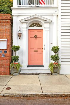 Let a cheerful paint color loosen up a formal facade. This coral shade peps up a Palladian transom, traditional pediment, and regal door knocker. Break from an otherwise symmetrical look with a single carriage lantern.Paint Color:Pink Mimosa (P180-3)