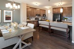 We love the splash back, the matching bar stools, and chairs in this glam kitchen and living space.