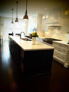 Beautiful open kitchen design with crisp white kitchen cabinets, calcutta marble counter tops & backsplash, ebony stained kitchen island and industrial yoke pendants.