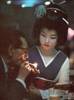 acamouflage:  Geisha presents a light to a diner in a Tokyo...
