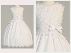 A Lovely White Cotton Blend First Holy Communion Dress with Beautiful 3 Dimensional Flowers and Leaves & Stem Embroidery on the Bodice, Scalloped Lace Waist, Satin Ribbon Trim, Tie Back Sash & Embroidered Lace Hemline.