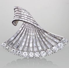 Sterlé - Platinum and Diamond Brooch - A French Mid-20th Century diamond and platinum brooch by Pierre Sterlé. This brooch is made in a dimensional stylized fan motif with a decorated edge of 12 round-cut diamonds with an approximate total weight of 12.60 carats, and a swirl of 168 baguette diamonds that have an approximate total weight of 20.25 carats. They have a VVS/VS clarity and E/F color grade.