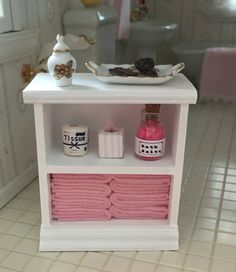 Dollhouse 1:12 scale Miniature  Adorable, White, wood, bathroom cabinet filled with pink towels, tissue, toilet paper and bath beads jar (Pieces are permanently attached)  Listing includes 1 bathroom cabinet (items shown on top of cabinet are not included in listing)  ***Notes: Other items shown in photos are used as props and are not included in this listing, but may be sold separately in our shop. Please remember this is a 1:12 scale dollhouse miniature, not for children under 14…