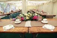 Wooden trestle tables were dressed with sack cloth runners decorated with lace in this beautiful vintage wedding marquee