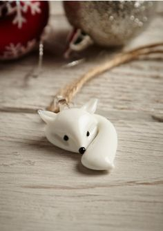 White Glass Fox Decoration. This super cute Christmas decoration features a white glass fox with bushy tail! This simple design would look lovely on your xma's