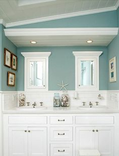 peinture murale en bleu clair, meubles blancs et déco de style bord de mer dans la salle de bains