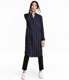 Mørkeblå/Stribet. Knælang kjole i vævet kvalitet. Kjolen har lav, opretstående krave, skjult lukning foran samt lange ærmer med manchet og trykknap. Snøre i