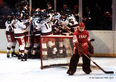 As USSR backup Goalie Vladislav Tretjak (20) contemplates his team's loss, Team USA celebrate their 4-3 upset defeat of the Soviets at the XIII Winter Olympics on February 22, 1980, at Lake Placid, N.Y. ~ Photo by Joe Lippincott