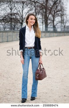 PARIS, FRANCE - MARCH 10, 2015: Stylish European woman with blue jeans in the Tuileries Garden. Paris Fashion Week: Ready to Wear 2015/2016 is held from March 3 to 11, 2015.
