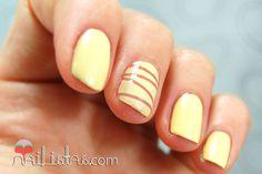 Uñas decoradas en amarillo con cinta para nail art