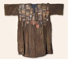 Africa | Hunter's shirt. Possibly Mossi peoples.  Burkina Faso | Mid 20th century | Cotton, leather, animal horns, iron bell | The wrapped packets are of leather, suggesting the shirt came from the cultivated world of a village. They often contain folded paper inscribed with passages from the Qur'an, Islam's sacred book, to invoke the power of the Word for protection.