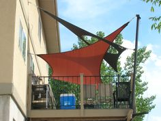 Intersecting shade sails over raised deck