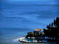 BLUE HEAVEN. A view of a small harbour and the deep blue sea. Corfu Greece.