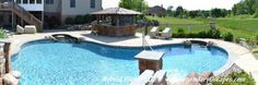 Hybrid Swimming Pool with Gunite Sun Ledge, raised spillover waterfall, waterslide and floating concrete countertop on this Hybrid Swimming Pool.